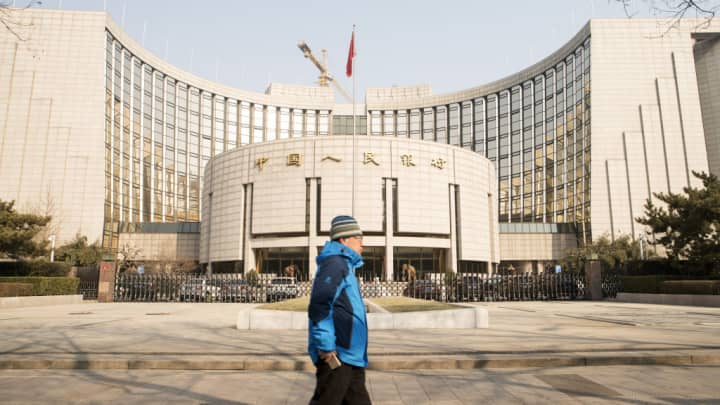 A pedestrian walks past the People's Bank of China headquarters in Beijing, China, on Monday, Feb. 26, 2018.