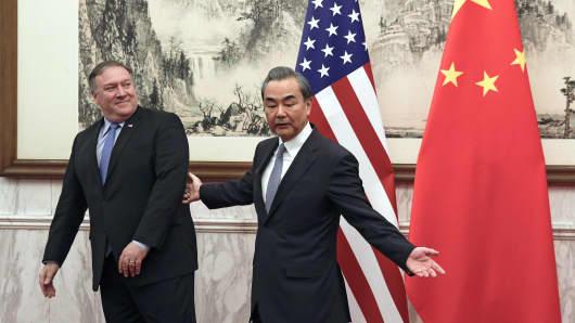 US Secretary of State Mike Pompeo (L) reacts as he is shown the way by China's Foreign Minister Wang Yi (R) before they proceed to their meeting at the Diaoyutai State Guesthouse in Beijing on October 8, 2018.