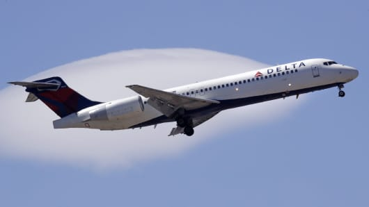 A Delta Air Lines passenger jet plane, a Boeing 717-200 model, approaches Logan Airport in Boston.