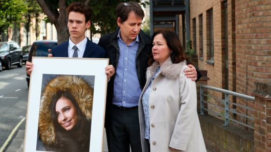 Nadim and Tanya Ednan-Laperouse, with their son Alex, prepare to speak to the media outside West London Coroners Court, Friday Sept. 28, 2018, following the inquest into the death of Natasha Ednan-Laperouse, 15, seen on poster, who died after suffering a fatal allergic reaction on a flight from London to Nice after eating a Pret a Manger sandwich at Heathrow Airport.