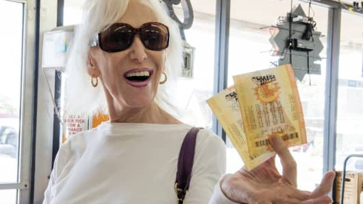 A woman jokingly holds up her Mega Millions Lotto tickets she purchased from Baycrest Wines & Spirits in Costa Mesa and proclaims, 'I've got the winning ticket.' (Photo by Leonard Ortiz/Digital First Media/Orange County Register via Getty Images)