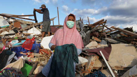 People look for usable clothing among rubble in the Petobo neighborhood which was hit by an earthquake and liquefaction in Palu, Central Sulawesi, Indonesia, October 8, 2018.