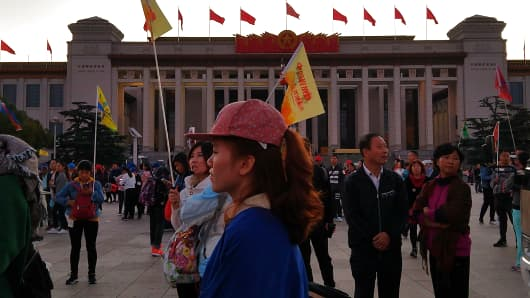 Tour guides, each holding a flag for their group, wait in front of the National Museum of China on the east side of Beijing's Tiananmen Square during a Golden Week flag-raising ceremony.