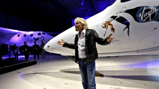 Sir Richard Branson walks around the new Virgin Galactic SpaceShipTwo at its roll out in the Mojave Desert, about a year and a half after Virgin's last rocket plane broke into pieces and killed the test pilot.