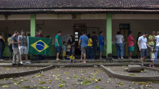 People queue to vote during general elections, in Vila Militar neighborhood, in Rio de Janeiro, Brazil, on October 7, 2018. - Brazilians cast ballots Sunday in their most divisive presidential election in years, with Jair Bolsonaro, a far-right politician promising an iron-fisted crackdown on crime, the firm favorite in the first round.