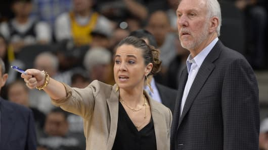 San Antonio Spurs assistant coach Becky Hammon, left, talks to Spurs head coach Gregg Popovich, right, on the court during a timeout in the second half of an NBA basketball game against the Los Angeles Lakers in San Antonio.