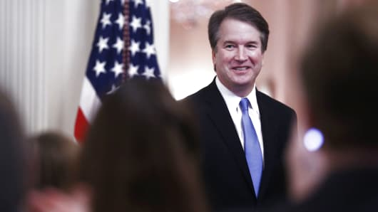 Brett Kavanaugh, associate justice of the U.S. Supreme Court, smiles as U.S. President Donald Trump, not pictured, speaks during a ceremonial swearing-in event in the East Room of the White House in Washington, D.C., U.S., on Monday, Oct. 8, 2018.