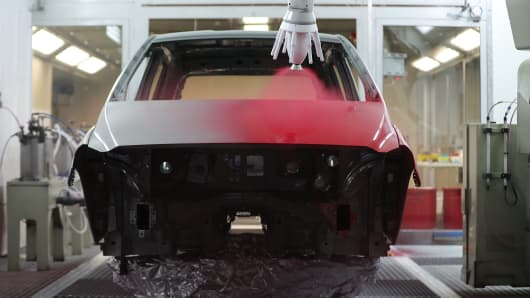 A robotic arm sprays red paint onto an automobile body at PPG Industries Inc.'s automotive coating's technical center in Ingersheim, Germany.