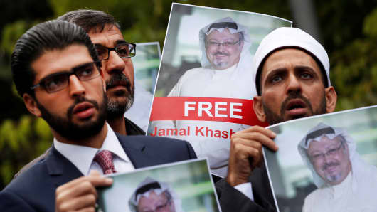 Human rights activists and friends of Saudi journalist Jamal Khashoggi hold his pictures during a protest outside the Saudi Consulate in Istanbul, Turkey October 8, 2018.