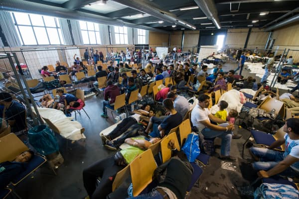Refugees who arrived in Germany by crossing the nearby Austrian border wait in the waiting zone at the X-Point Halle initial registration center of the German federal police (Bundespolizei) on July 15, 2015 near Passau, Germany.