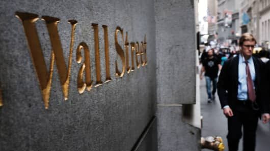 People walk outside of the New York Stock Exchange.