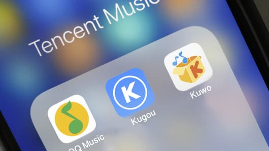 The logos of QQ Music, Kugou and Kuwo are seen on the screen of an iPhone on June 12, 2018 in Paris, France. QQ Music, Kugou and Kuwo are the three streaming Chinese music services owned by Tencent.