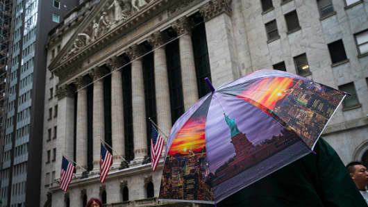 A man holds a New York City-themed umbrella outside the New York Stock Exchange (NYSE) on a rainy day in the Financial District, October 11, 2018 in New York City.