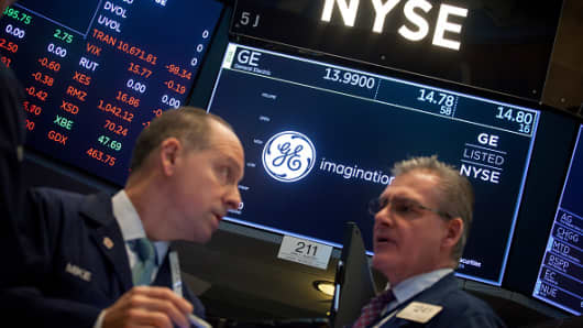 Dealers work under a monitor displaying the signage of General Electric Co. on the floor of the New York Stock Exchange.