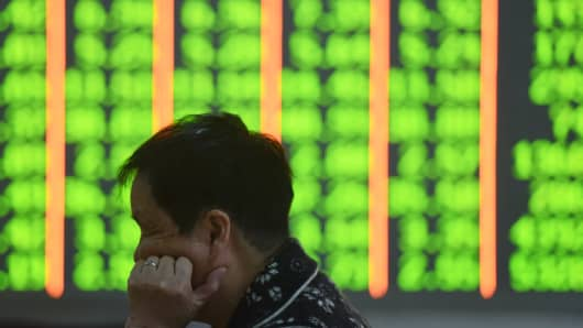 An investor watches the electronic board at a stock exchange hall on October 11, 2018 in Hangzhou, Zhejiang Province of China.