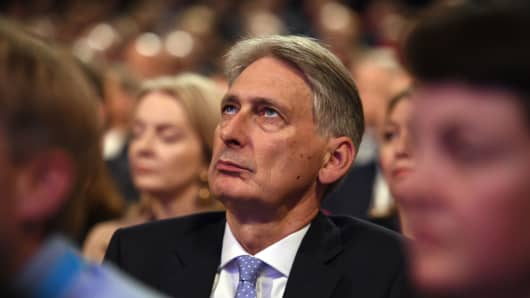 Britain's Chancellor of the Exchequer Philip Hammond waits for Britain's Prime Minister Theresa May to give her keynote address on the fourth and final day of the Conservative Party Conference 2018 at the International Convention Centre in Birmingham, central England, on October 3, 2018.