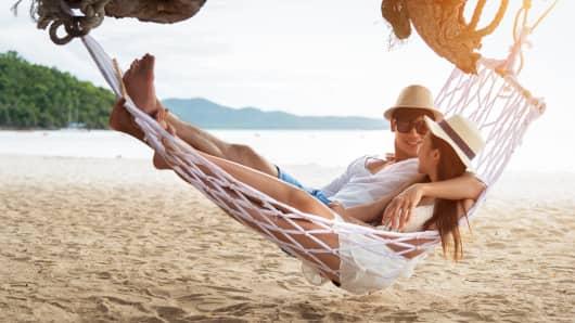 Asian couple lying on hammock on beach thailand