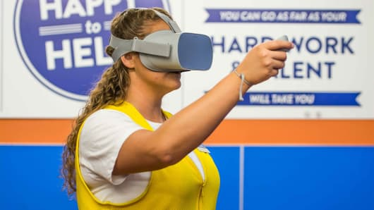 Caption: Walmart employee trains on Oculus VR headset