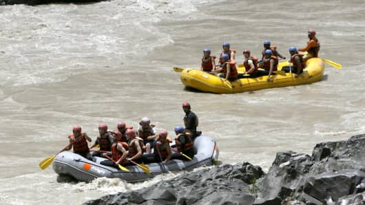 Foreign tourists take part in white water rafting on India's Zanskar river.