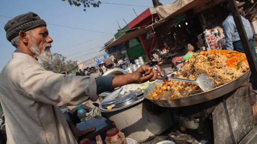 A man cooking chicken biryani in the old city of Delhi in India.