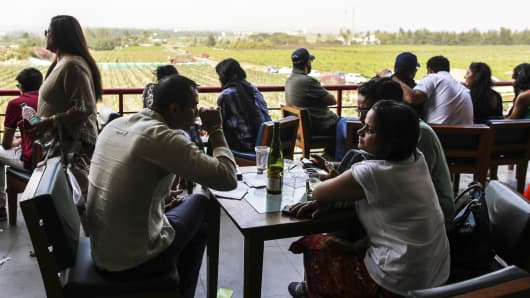 Customers sit drinking wine during a festival in the Nashik Valley, Maharashtra, India.