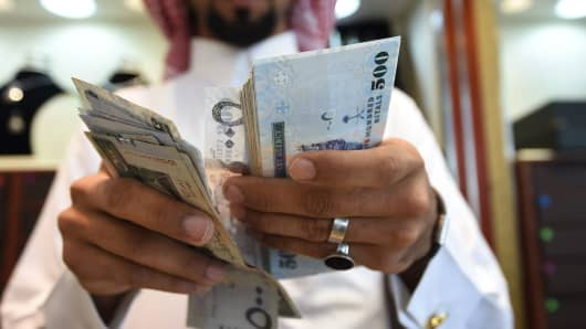 A man counts Saudi riyal banknotes at his jewelry shop in Tiba market in the capital Riyadh on October 3, 2016.