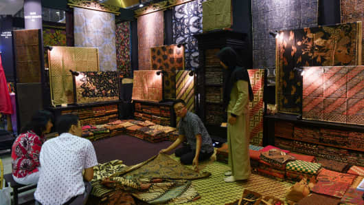 "Vendors selling Indonesian traditional fabric known as ""batik"", a technique of wax-resist dyeing applied to whole cloth, from Solo during a craft exhibition in Jakarta on Sept. 12, 2018."
