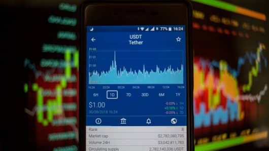 A smartphone displays the Tether market value on the via The Crypto App.