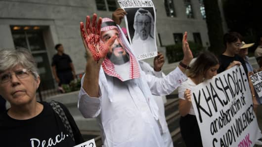 A demonstrator dressed as Saudi Arabian Crown Prince Mohammed bin Salman (C) with blood on his hands protests outside the Saudi Embassy in Washington, DC, on October 8, 2018, demanding justice for missing Saudi journalist Jamal Khashoggi.