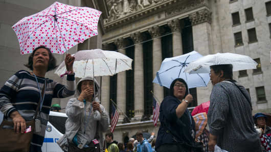 Tourists hold umbrellas as they walk past the New York Stock Exchange.