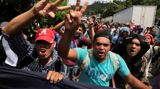 Honduran migrants, part of a caravan trying to reach the U.S., gesture while arriving to the border between Honduras and Guatemala, in Agua Caliente, Guatemala October 15, 2018.