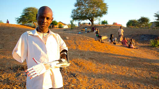 Daniel Omar, a South Sudanese boy who lost both of his arms at age 14 to a bomb that exploded in that war-torn country, with the 'Robohand' prosthetic invented using a 3-D printer.