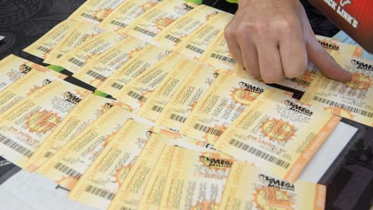 A clerk counts out the $300 worth Mega Millions Lotto tickets purchased by a customer.