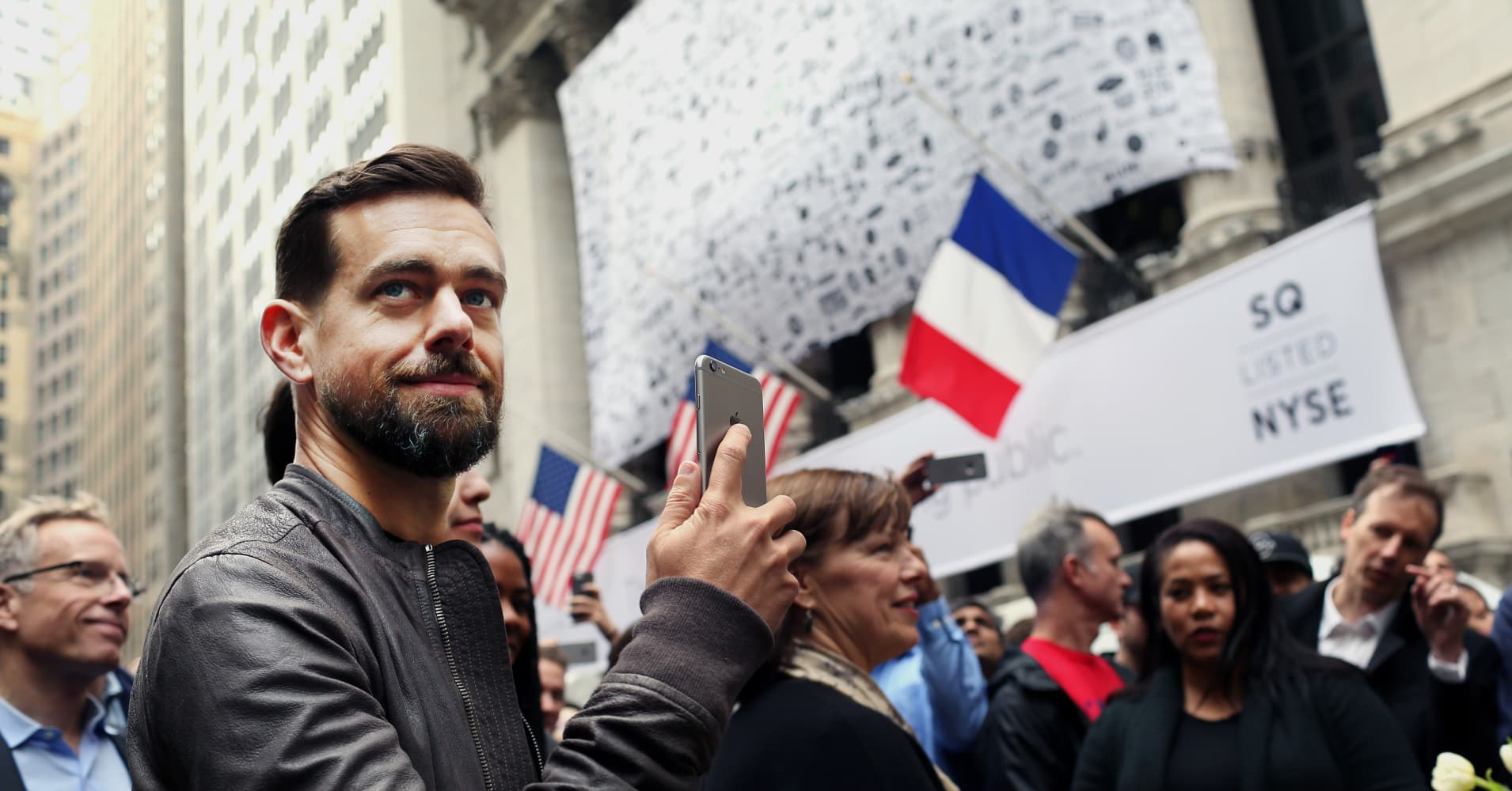 Jack Dorsey, CEO of Square Inc., holds an Apple Inc. iPhone while standing outside of the New York Stock Exchange (NYSE) in New York, U.S., on Thursday, Nov. 19, 2015.