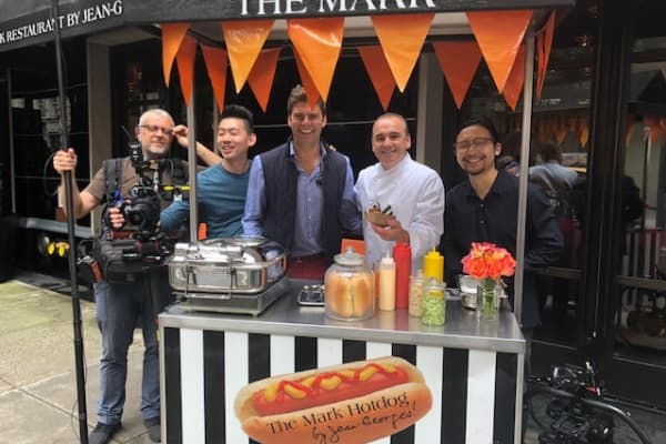 CNBC producer Chris DiLella and film crew with chef Jean-Georges Vongerichten at his hot dog stand outside the Mark Hotel in New York City.