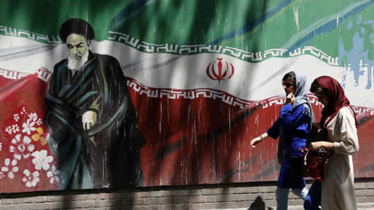 Iranians walk by a mural painting of Ayatollah Ruhollah Khomeini, the founder of the Islamic Republic, on the wall of the former U.S. embassy in Tehran on August 7, 2018.