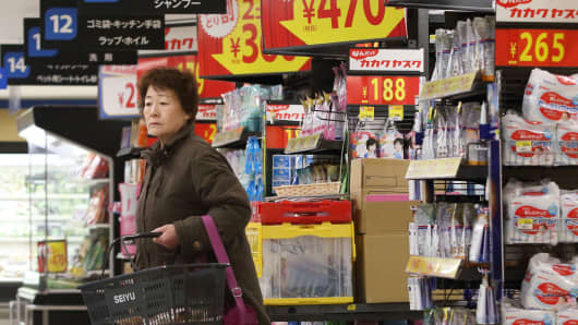 Signage displays sale prices as a customer shops at a Seiyu supermarket in Tokyo, a discount chain owned by Walmart Stores.