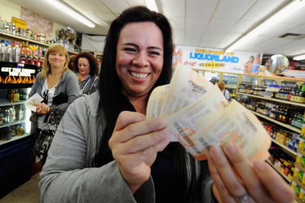 Victoria Vazquez displays $280 worth of Mega Millions lottery tickets for her office pool on March 30, 2012.