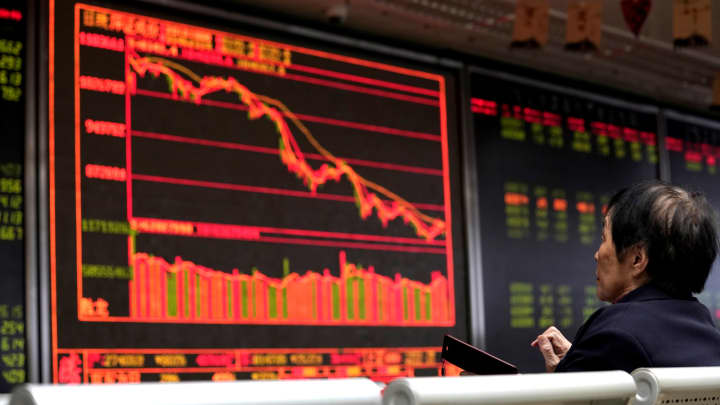 An investor watches a board showing stock information at a brokerage office in Beijing, China.