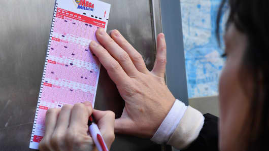 A woman fills out a Mega Millions lottery ticket on October 19, 2018 in New York City. The Mega Millions jackpot is currently up to $970 million.