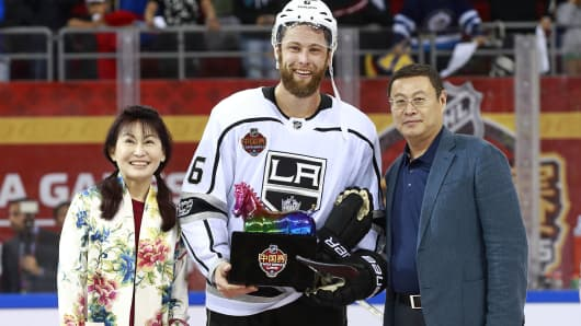 BEIJING, CHINA - SEPTEMBER 23:  Madam Zhao and Zhou Yunjie present Jake Muzzin #6 of the Los Angeles Kings with the MVP trophy after the pre-season game against the Vancouver Canucks at Cadillac Arena September 23, 2017 in Beijing, China. The Kings won 4-3 in a shootout.