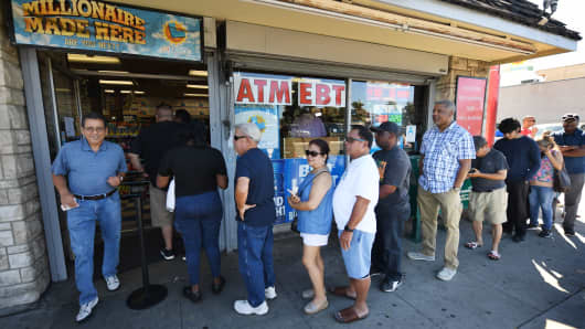 Customers buy Mega Millions tickets hours before the draw of the $1 billion jackpot, at the Blue Bird Liquor store in Hawthorne, California, on October 19, 2018.