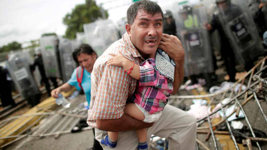 A Honduran migrant protects his child after fellow migrants, part of a caravan trying to reach the U.S., stormed a border checkpoint in Guatemala, in Ciudad Hidalgo, Mexico October 19, 2018. REUTERS/Ueslei Marcelino TPX