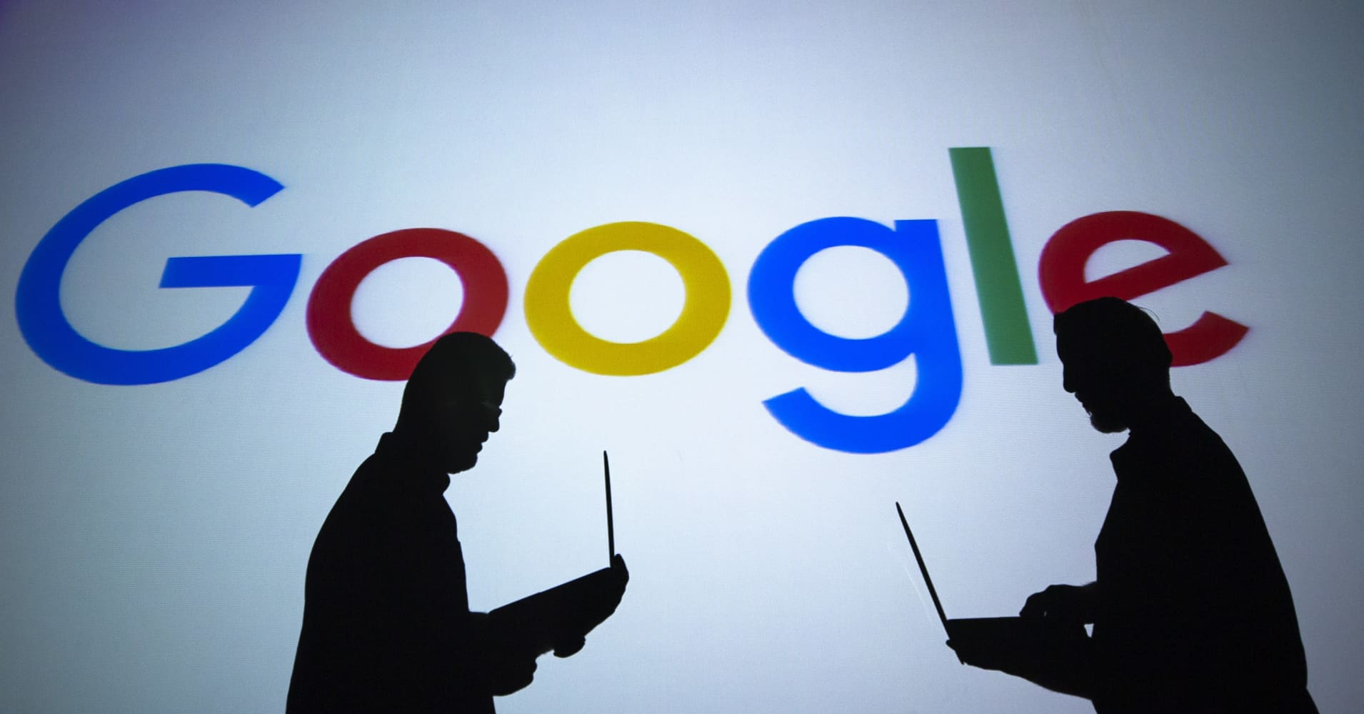Silhouettes of people holding laptops are seen in front of the logo of 'Google' technology company.