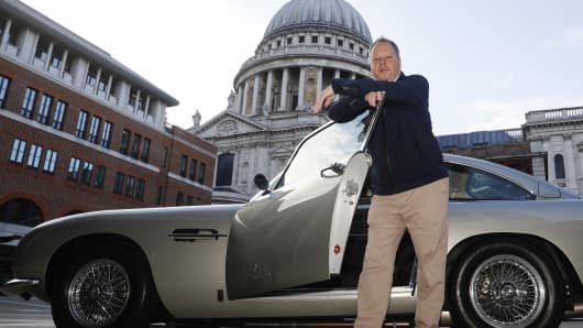 Andy Palmer, chief executive officer of Aston Martin Lagonda Global Holdings Plc, poses for a photograph with an Aston Martin DB5 automobile outside the London Stock Exchange in London, U.K., on Wednesday, Oct. 3, 2018.