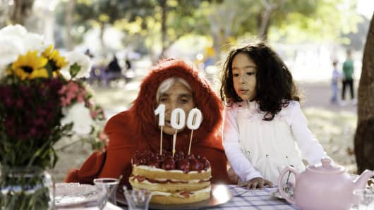 Ederly Woman And Grandson Bowing Birthday Cake