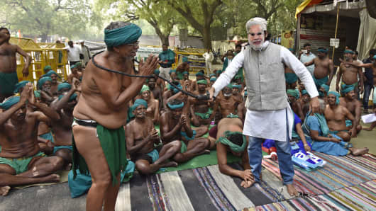 A man wearing PM Modi's mask and beats a Tamil Nadu farmer during a play as part of protest seeking compensation for drought in the state, at Jantar Mantar on April 18, 2017 in New Delhi, India.