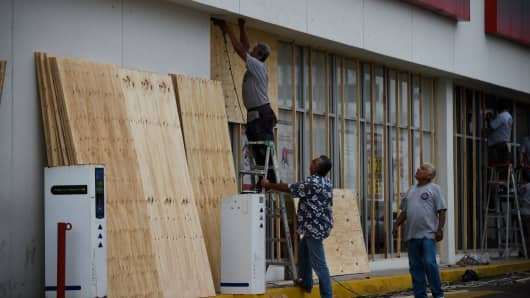 Workers protect a storefront with wood panels at the Mazatlan port in Sinaloa state, Sinaloa state, Mexico, on October 22, 2018, before the arrival of Hurricane Willa.