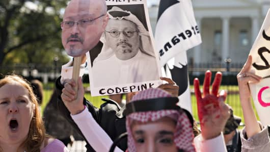 Demonstrators hold photographs of journalist Jamal Khashoggi outside the White House in Washington, D.C., on Friday, Oct. 19, 2018.