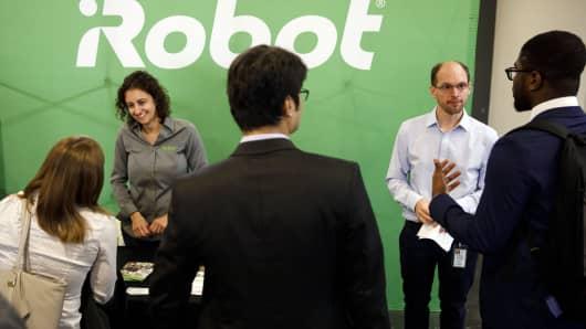 iRobot Corp. representatives speak with job seekers during the TechFair LA career fair in Los Angeles.